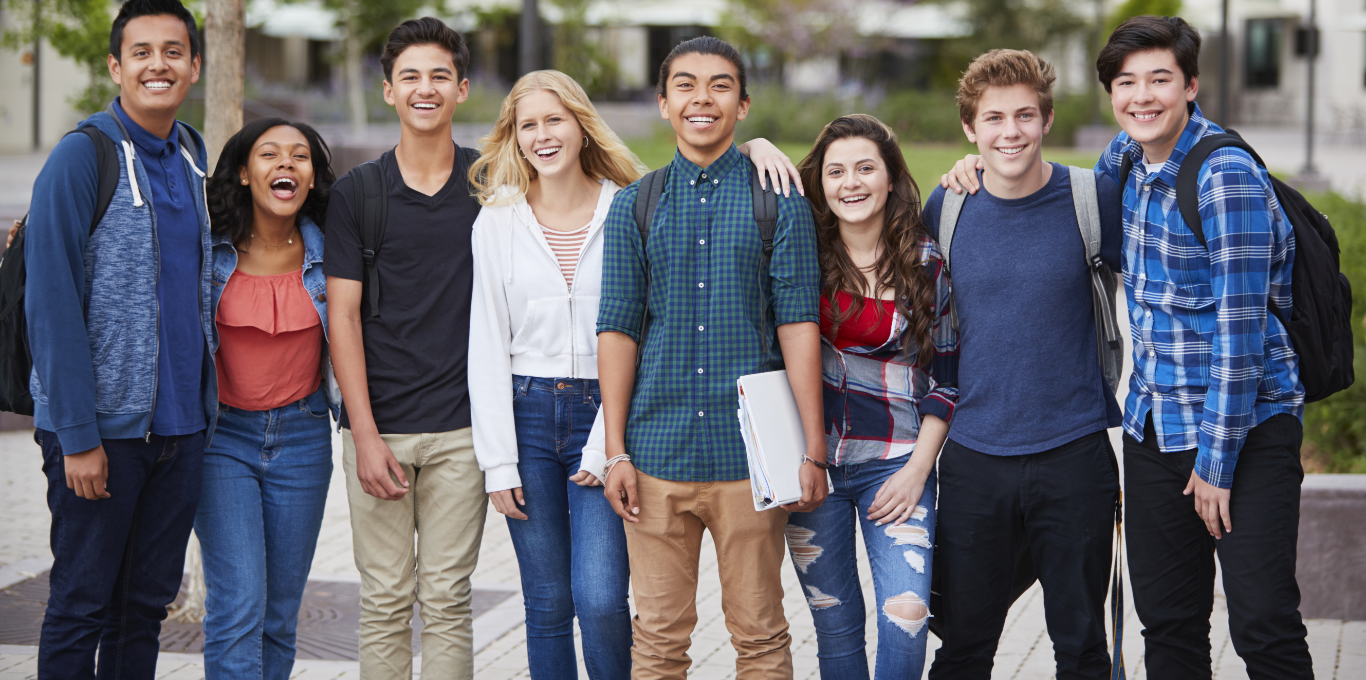 Eight students stand one beside the other and smiling. A student in the center holds a binder in his hand.