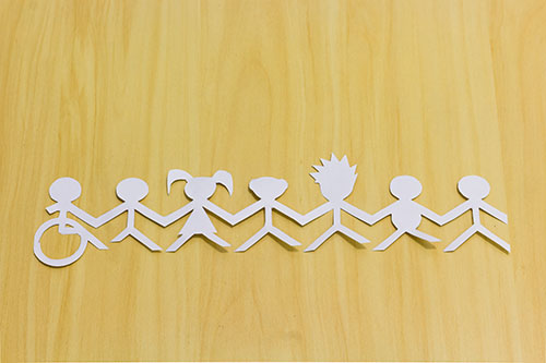 A paper cut-out shows a row of seven children holding hands. The first child is in a wheelchair.